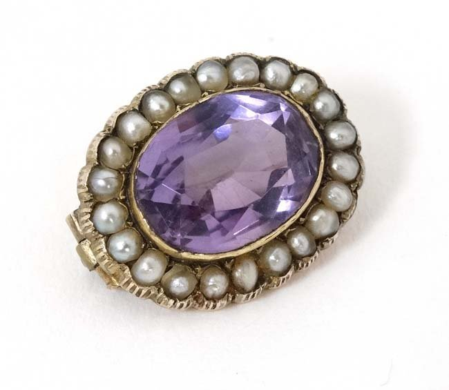 A gilt metal brooch set with central amethyst bordered