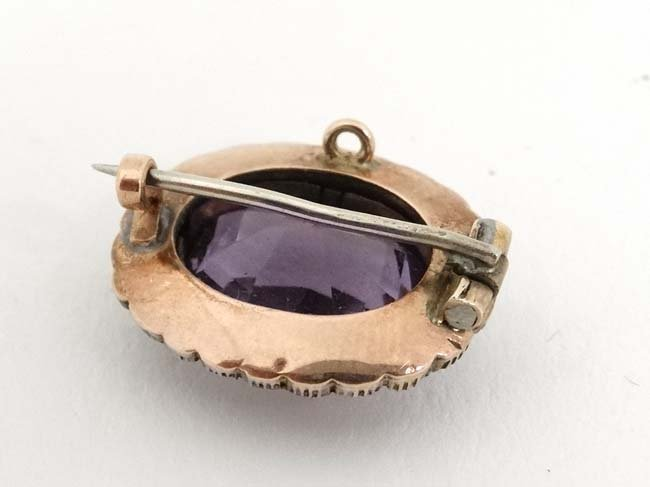 A gilt metal brooch set with central amethyst bordered - 2