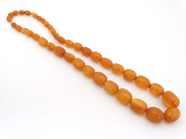 A string of graduated amber coloured beads approx. 24''