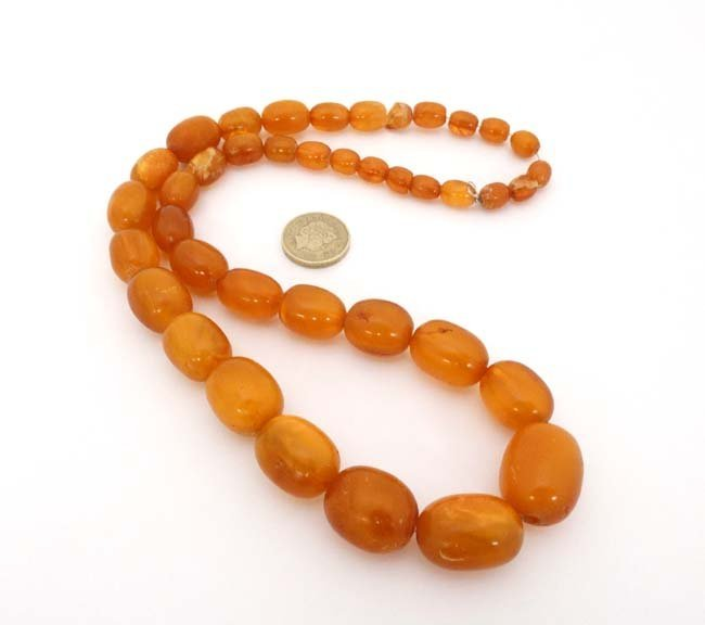 A string of graduated amber coloured beads approx. 24'' - 2