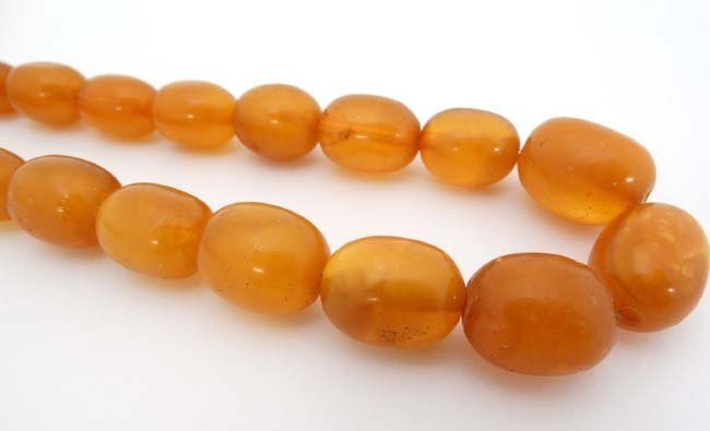 A string of graduated amber coloured beads approx. 24'' - 3