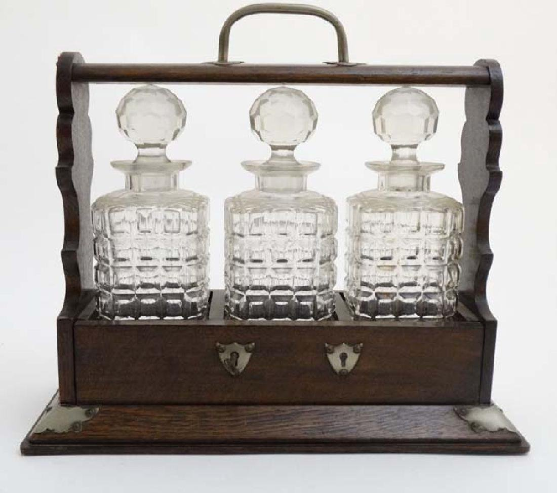 A late 19thC / early 20thC 3- bottle oak Tantalus with