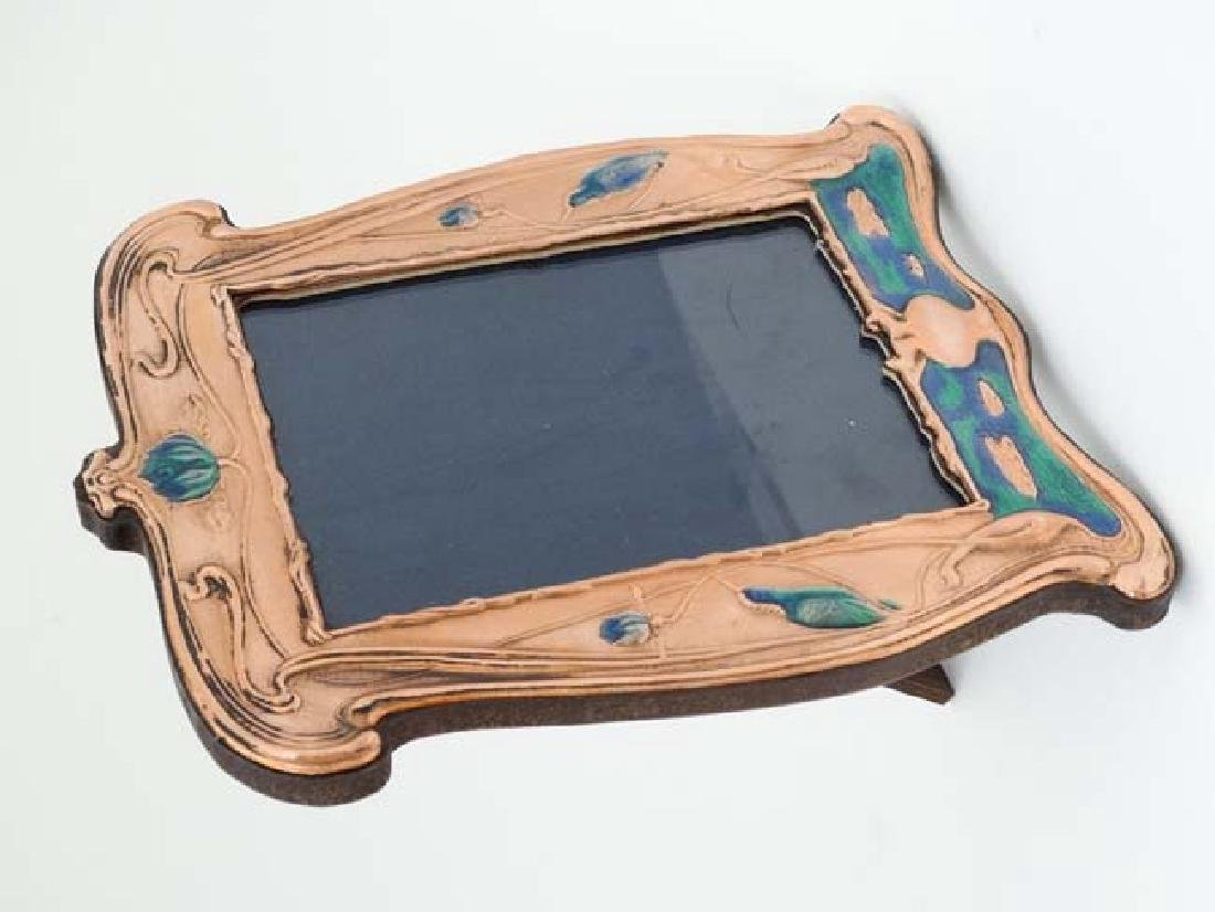 A 21stC photograph frame with embossed copper surround
