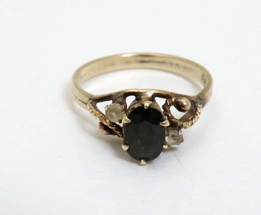 A gold ring set with dark semi-precious stone flaked by