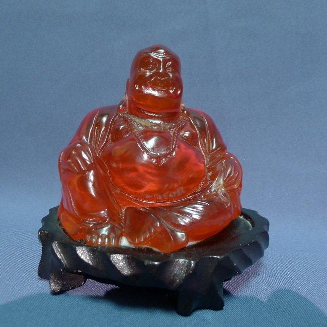 A Chinese red amber sitting buddha.