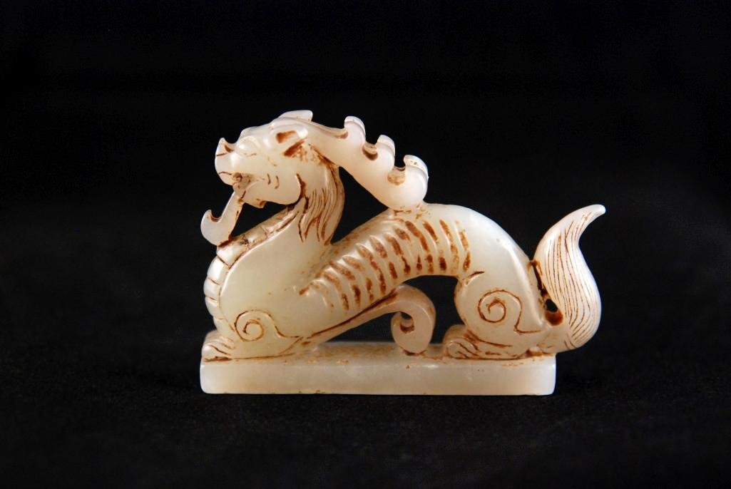 16: A SMALL WHITE MOTTLED JADEITE DRAGON CARVING