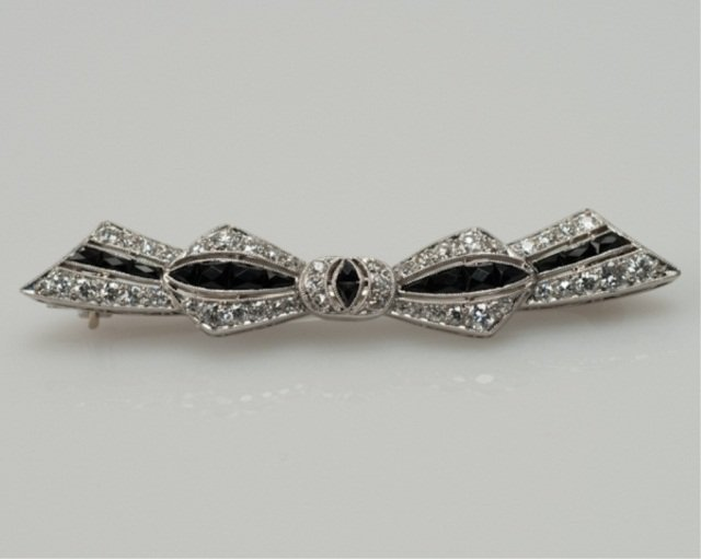 125: A Platinum, Diamond and Black Onyx Art Deco Bow Br
