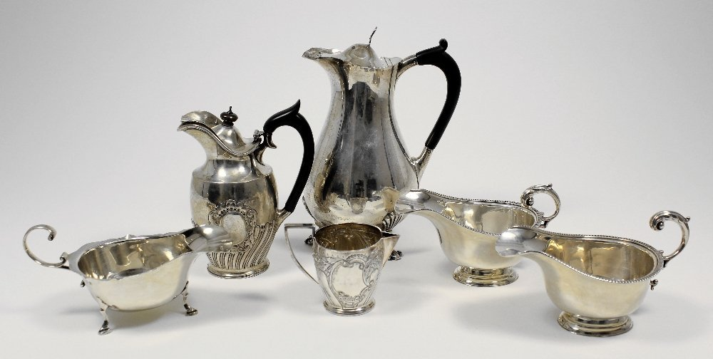 A George V silver bulbous hot water jug with shaped rim