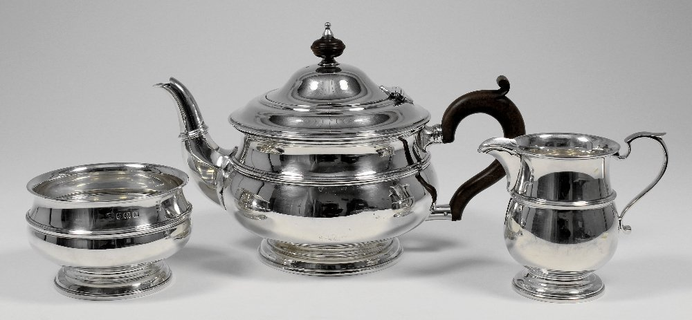 A George V silver circular three piece tea service with