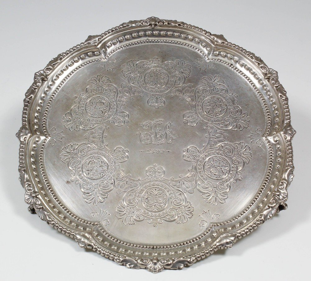 A late Victorian silver salver, the shaped rim with she