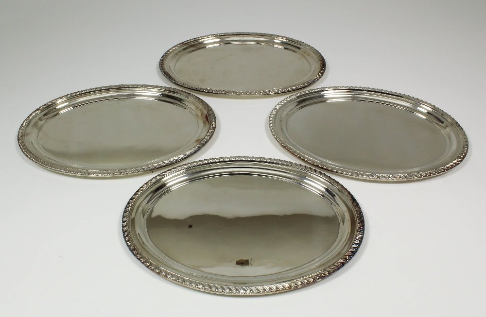 Four Elizabeth II silver oval dishes with gadroon mount