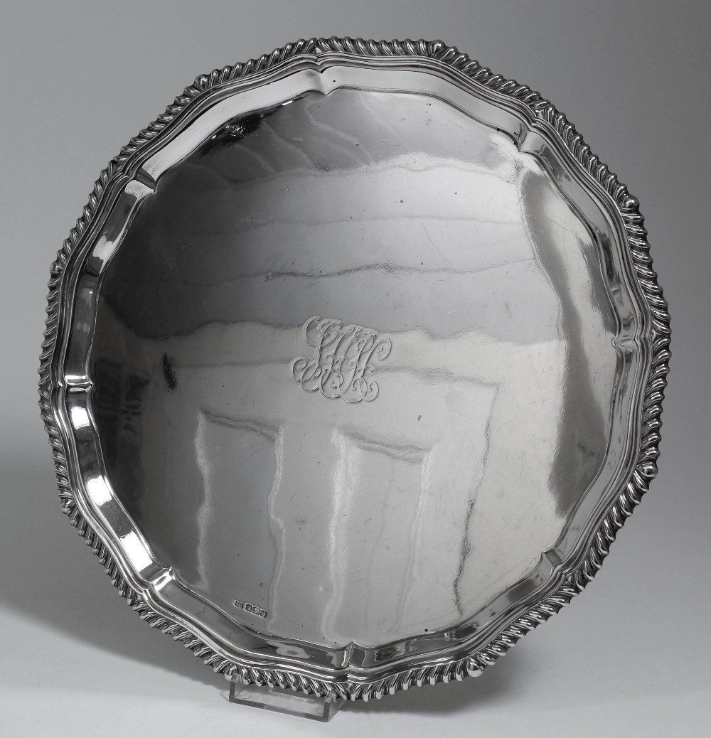 A George V silver circular salver, the shaped and mould