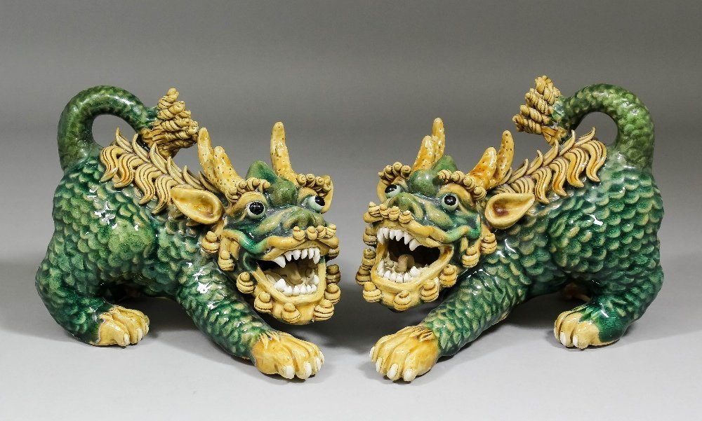 A pair of Chinese pottery models of crouching Dogs of F