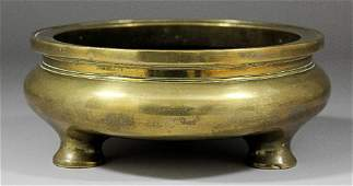 A Chinese bronze censer of squat circular form on three