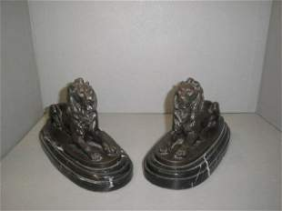 A pair of bronze recumbent lions on a marble plinth