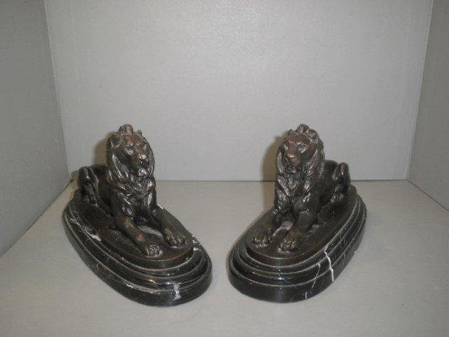 10: A pair of bronze recumbent lions on a marble plinth