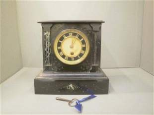 A slate mantle clock set with marble pilasters.
