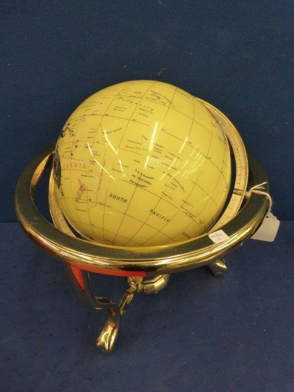 A brass and semi-precious inlaid tabletop globe.