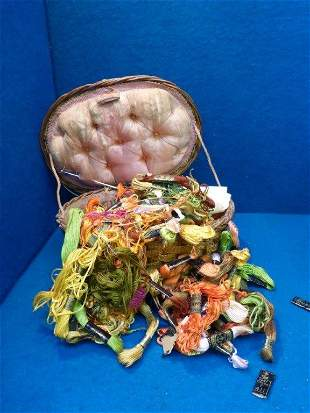 A basket with a quantity of embroidered silks.