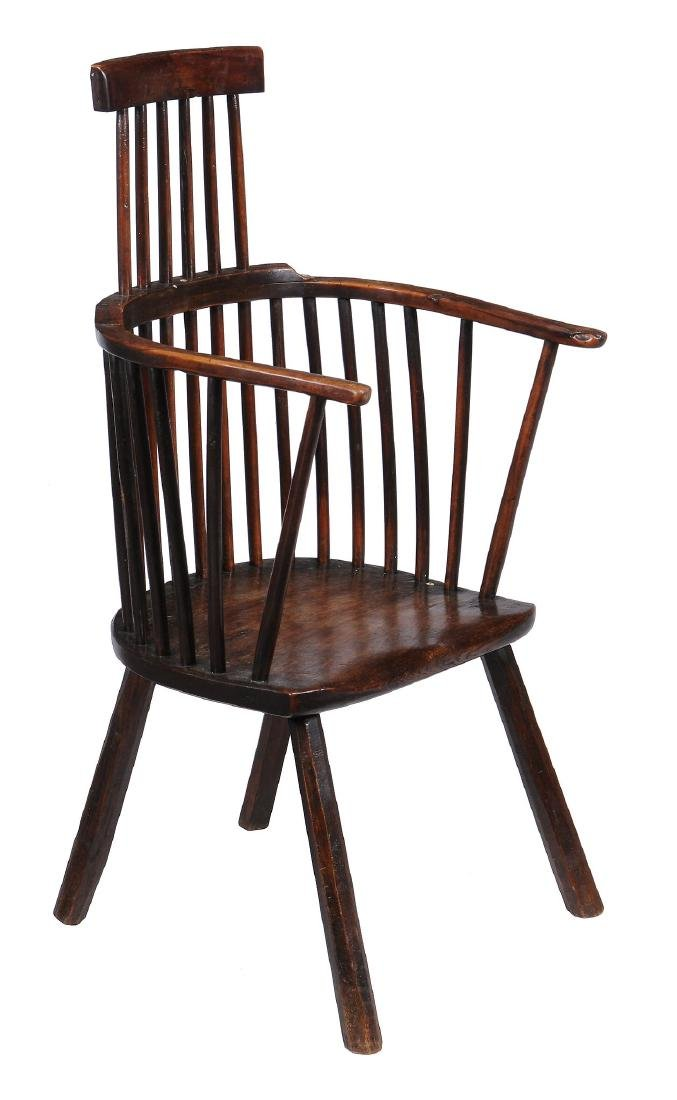 A walnut and fruitwood comb back armchair , circa 1800
