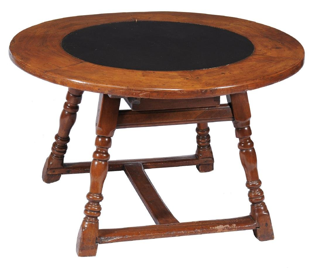 A Continental walnut and slate inset circular dining or