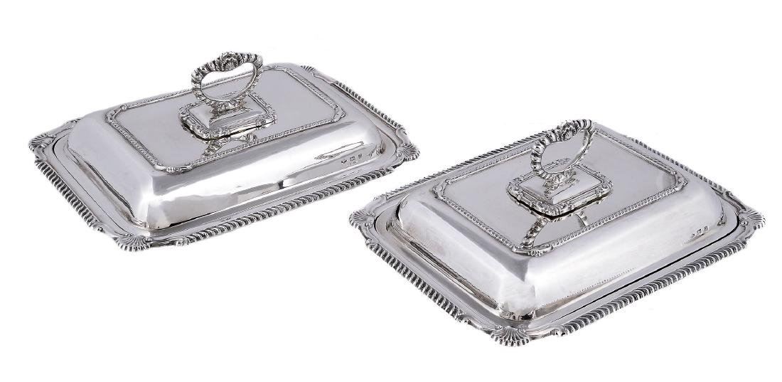 A pair of silver rectangular entree dishes and covers