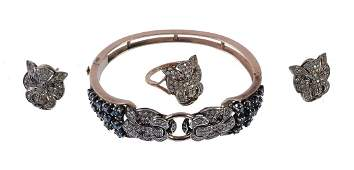 A diamond sapphire and ruby lion head hinged bangle