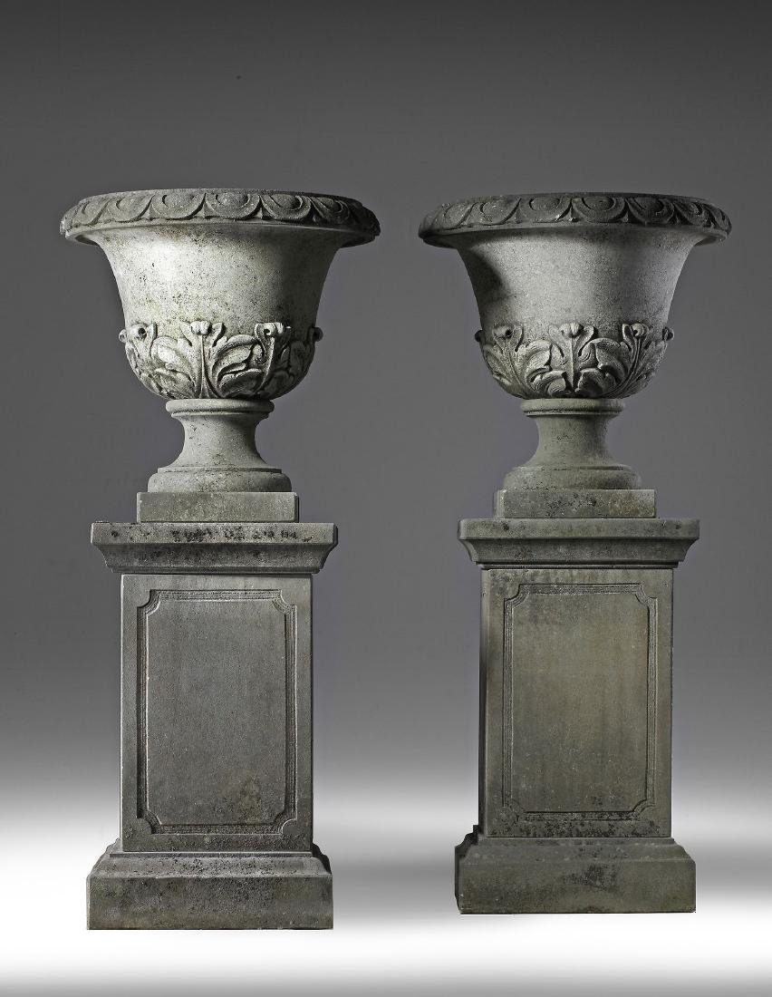 pair of carved limestone garden urns on plinths ,