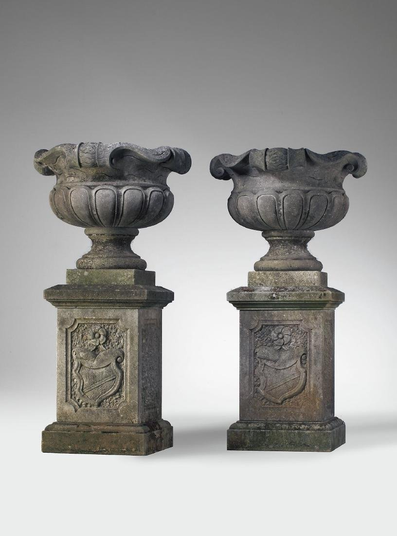 A pair of continental carved limestone garden urns on