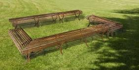 A set of five wrought iron garden benches constituting