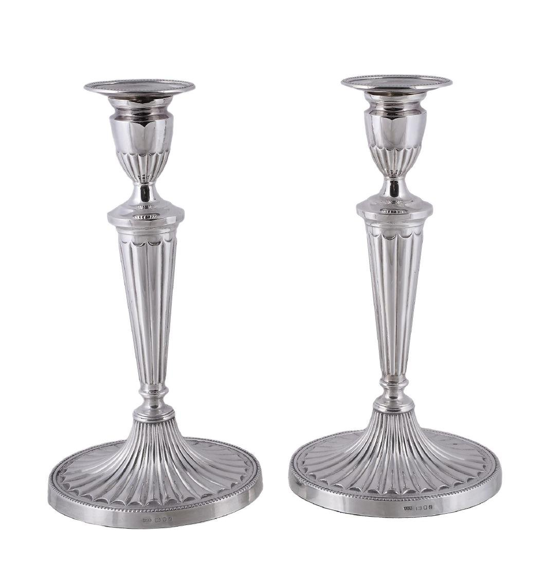 A pair of silver candlesticks by Roberts & Dore Ltd