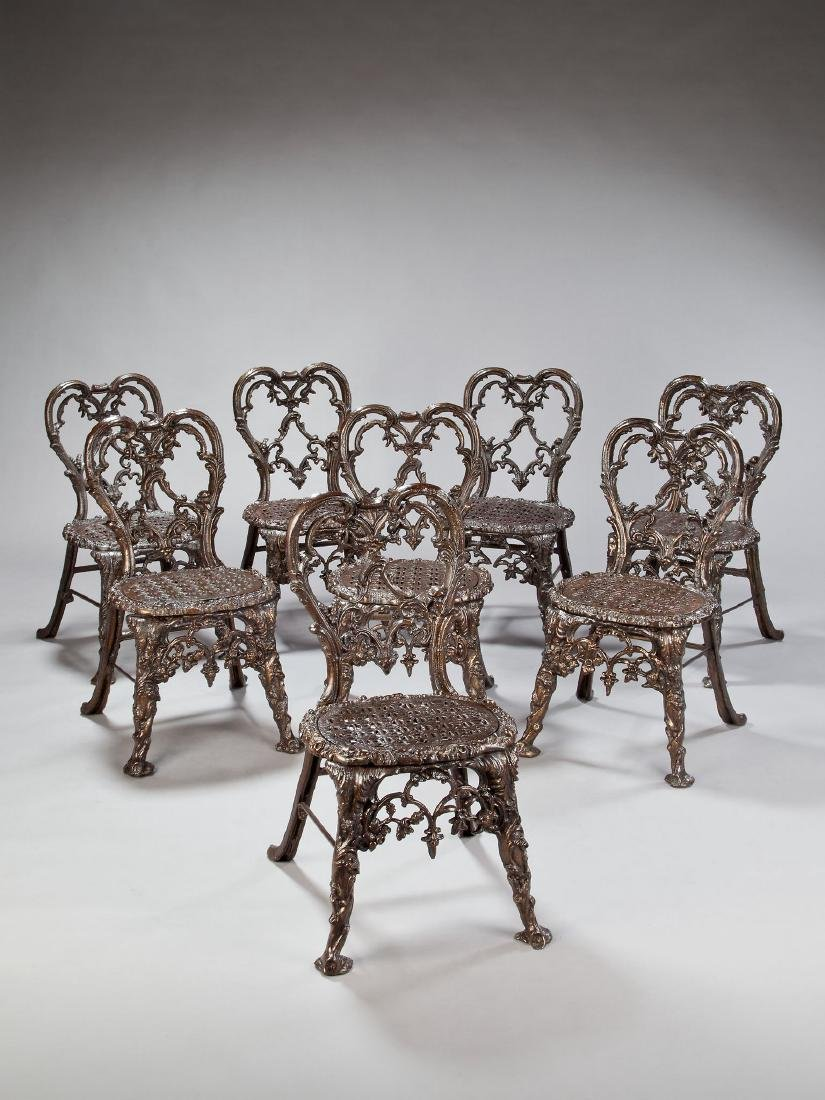 A matched set of eight cast metal garden chairs in a