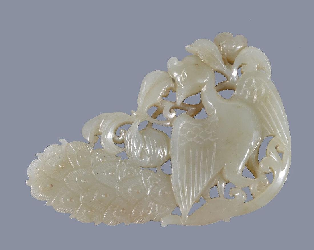 A Chinese pale celadon and russet 'peacock' pendant