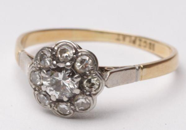 A nine stone diamond cluster ring, the central bri