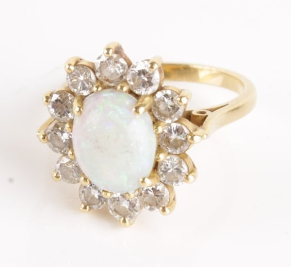 An opal and diamond cluster ring, the oval cabocho