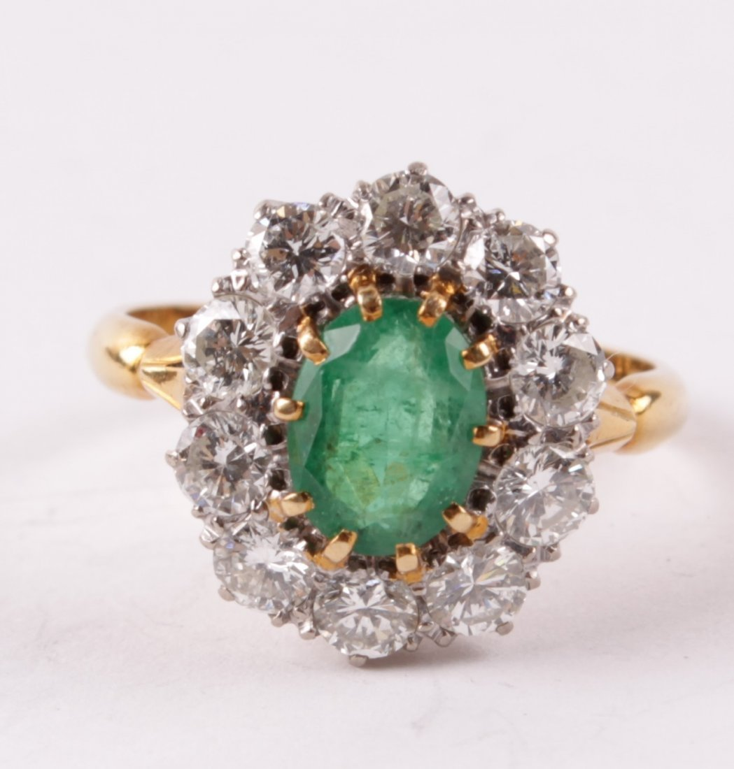 A diamond and emerald cluster ring, the oval cut e