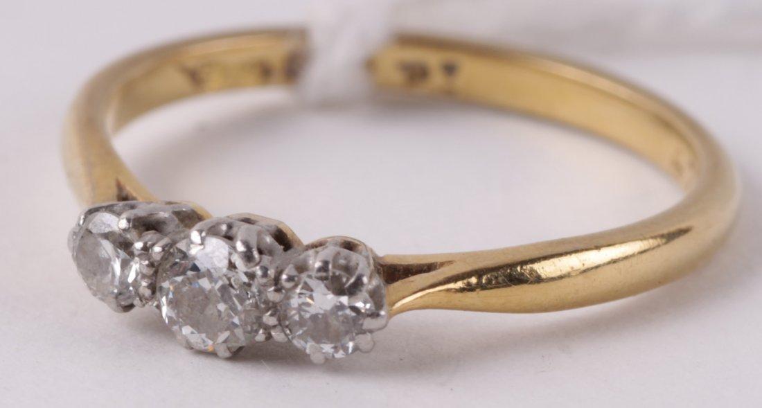 A three stone diamond ring, the brilliant cuts tot