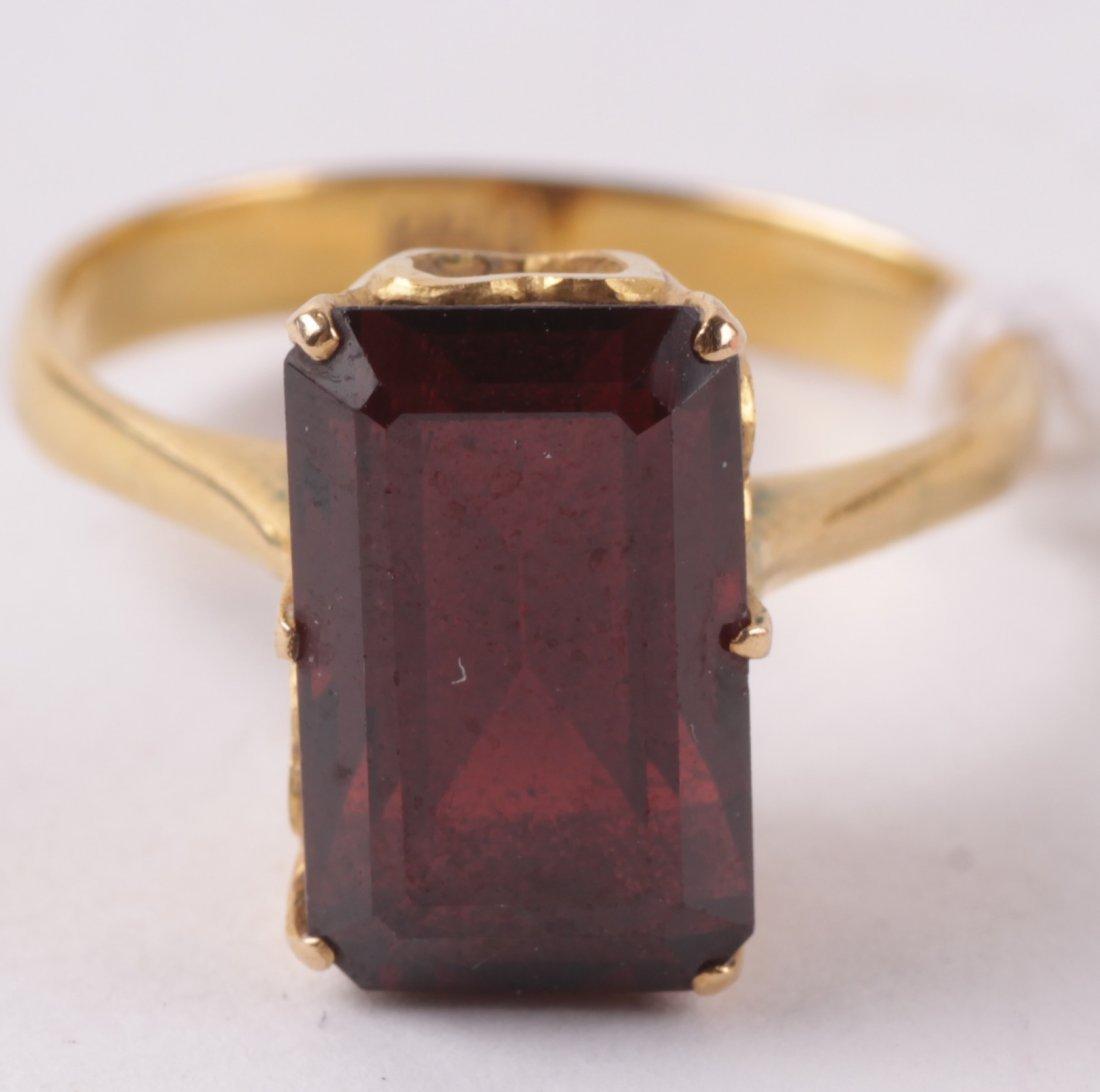 A single stone garnet ring, the step cut stone in
