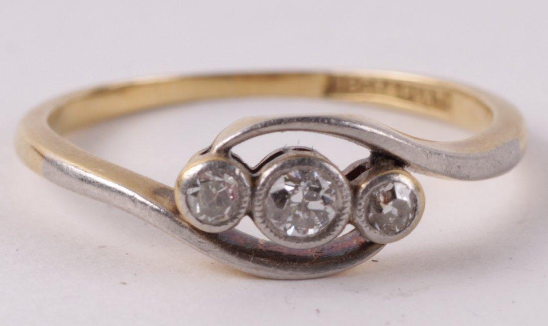 A three stone diamond cross over ring, the graduat