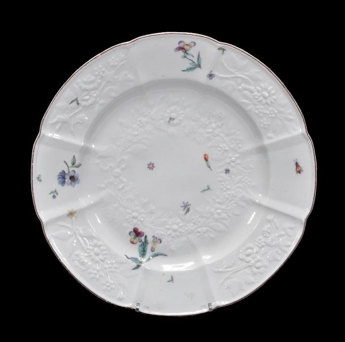 A Chelsea relief-moulded plate , decorated in low