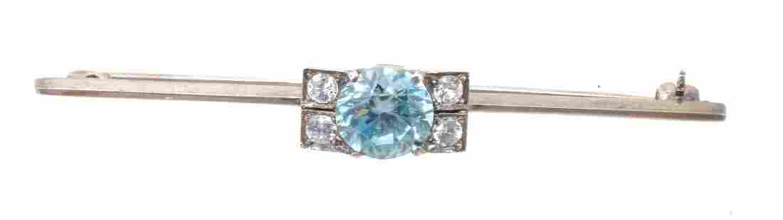 A zircon bar brooch, the central circular cut blue