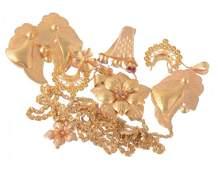A gold coloured flower head pendant and ear pendants;