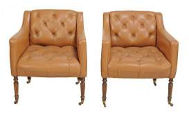 A pair of leather button back upholstered armchairs