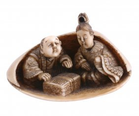 An Ivory Netsuke Depicting A Man And A Woman Sheltering