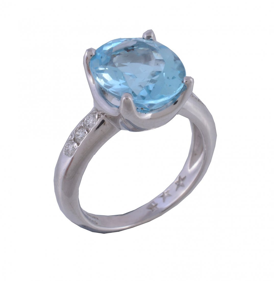 A blue topaz and diamond ring , the oval cut topaz in a