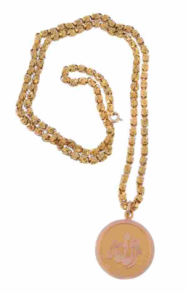 A gold coloured chain and pendant, the circular pendant