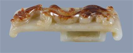 A Chinese russet and celadon jade belt hook