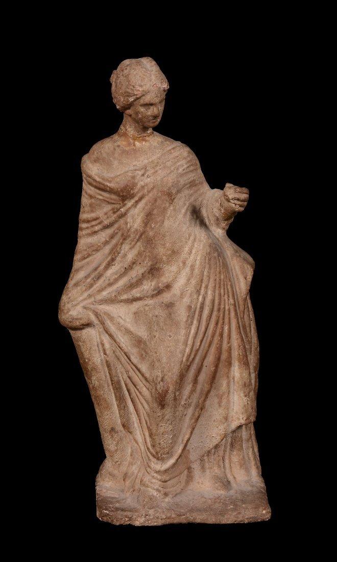 A terracotta statuette of a female enveloped in a