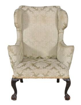 A mahogany and upholstered wing armchair in George I