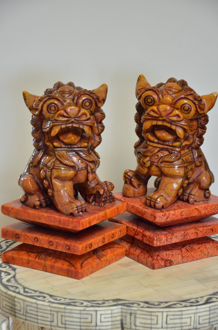 PAIR OF RED STONE CARVED FOO DOGS